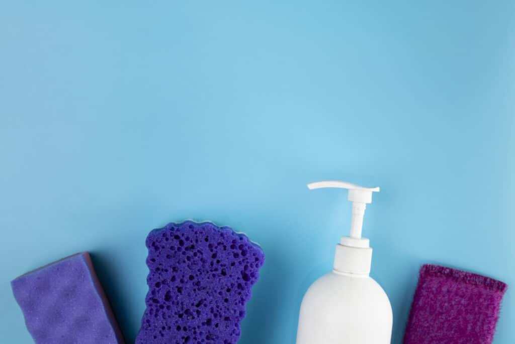 Imagem mostra tipos de espojas nas cores azul e roxo e um recepiente plástico branco. Ilustração do texto sobre como limpar banco de couro.