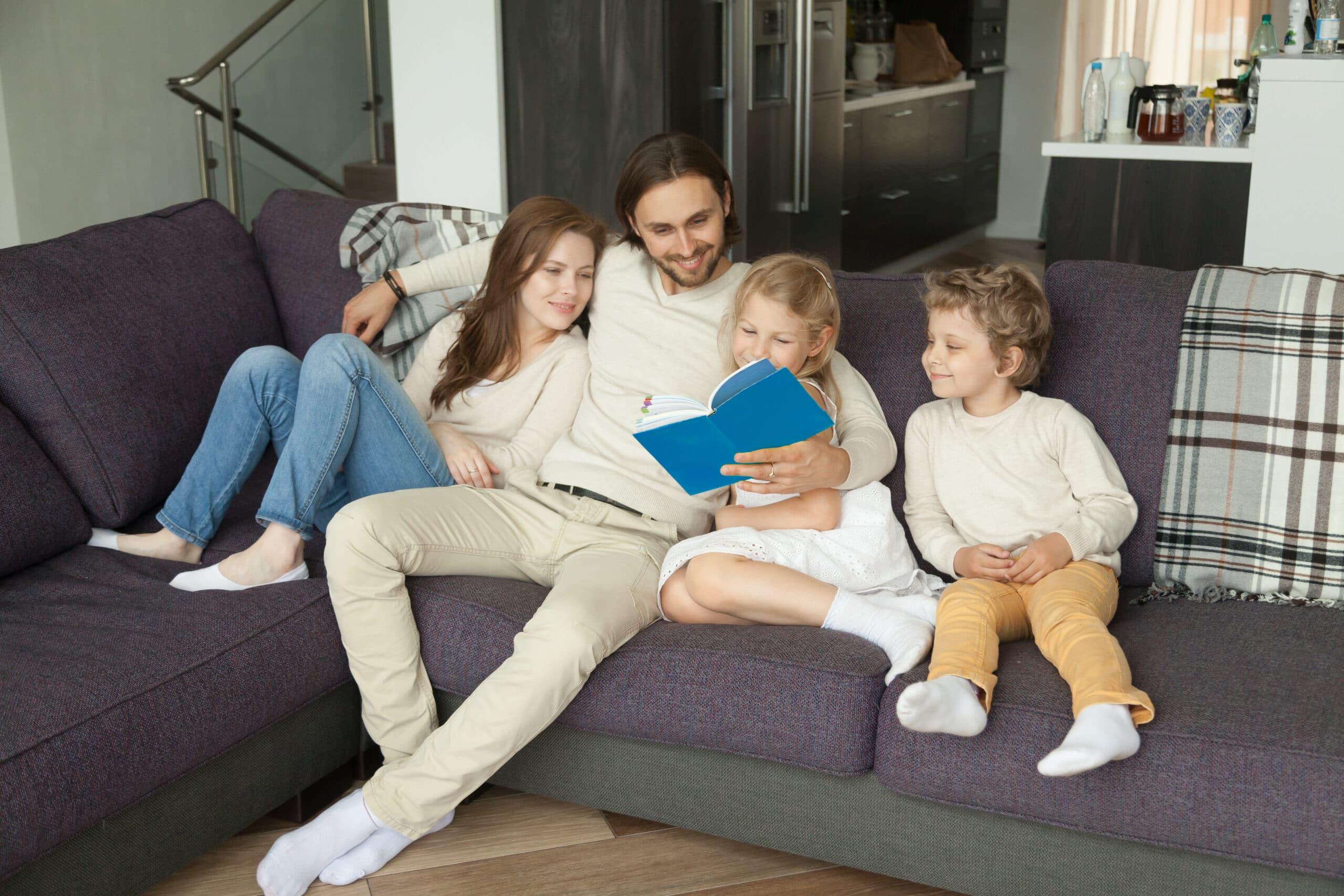 Família composta por pai, mãe, um menino e uma menina, sentados em um sofá lendo um livro.