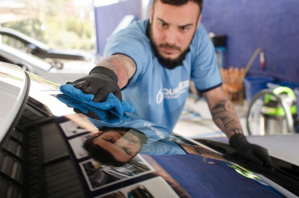 Funcionário da Acquazero fazendo processo de limpeza no vidro do carro