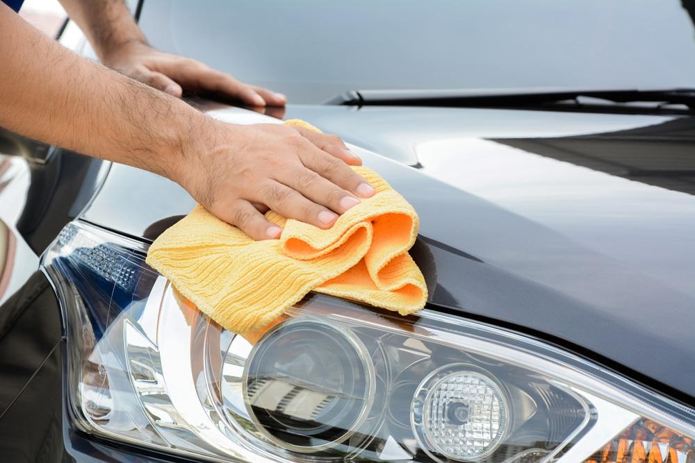 Homem fazendo a limpeza do capó de um carro