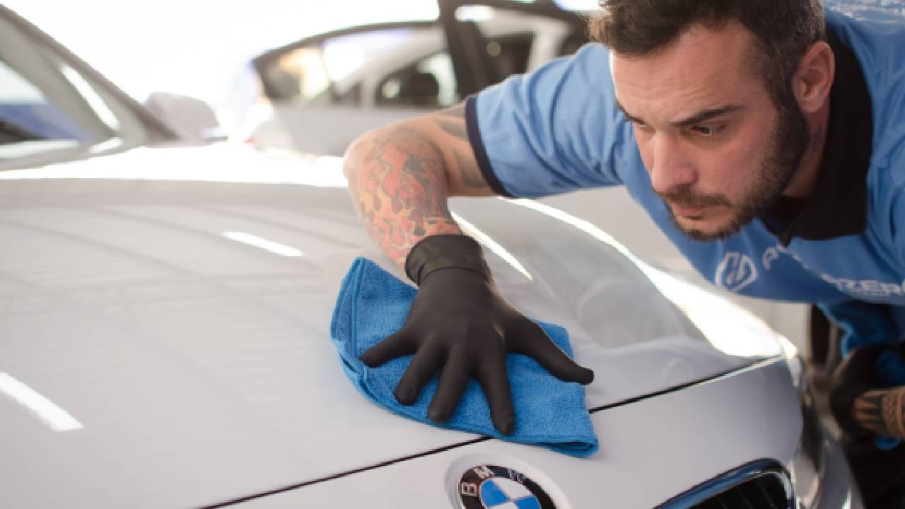 Funcionário Acquazero trajando blusa azul e luvas pretas, higienizando um carro branco com o auxílio de um tecido na cor azul. Imagem ilustrativa do texto limpar carro em casa Natal.