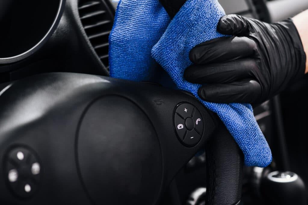 Foto focada na mão de uma pessoa com luva preto usando um pano azul para higienizar um volante preto de carro. Imagem ilustrativa para o texto Polimento automotivo em aracaju.