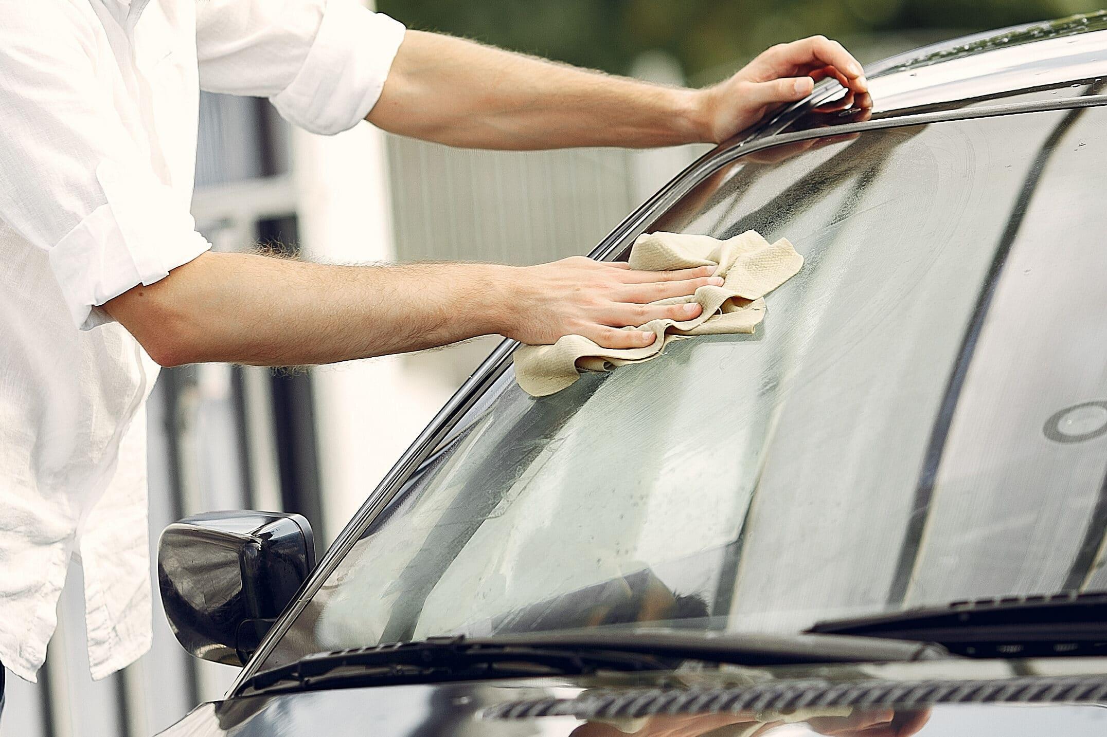 Homem de roupa branca utilizando um pano bege para a fazer a limpeza do vidro de um carro marrom que está ao seu lado. Imagem ilustrativa para o texto Polimento automotivo em aracaju.