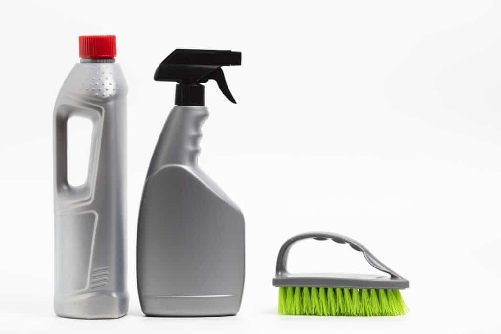 Três objetos de limpeza na cor cinza. Um frasco de produto com tampa vermelha, um borrifador de tampa preta e uma escova com cerdas verdes. Imagem ilustrativa para o texto limpeza de couro.