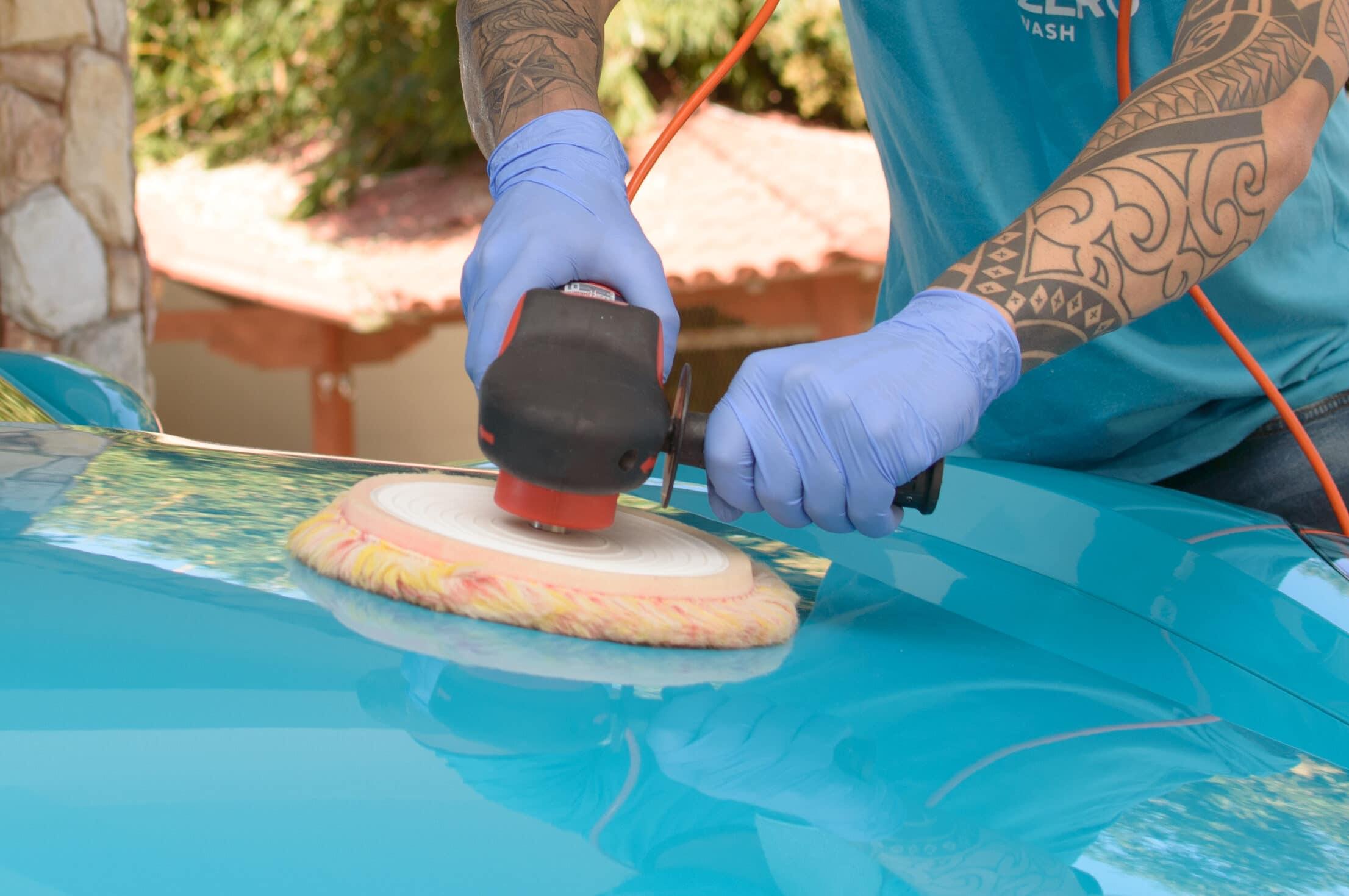 Profissional da Acquazero com o uniforme azul da empresa, segurando uma politriz para fazer o polimento na pintura de um carro azul. Imagem ilustrativa para o texto Polimento automotivo em aracaju.