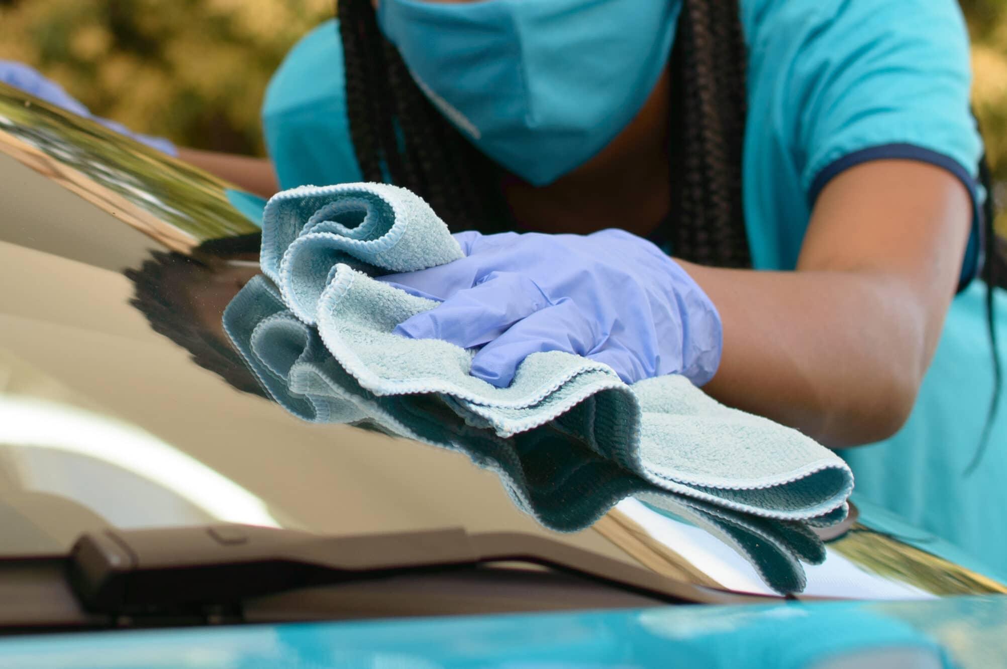 Funcionária da Acquazero usando uniforme azul e luvas azul realizando o procedimento de cristalização de vidros em um carro também azul. Imagem ilustrativa para o texto lava rápido buritis.
