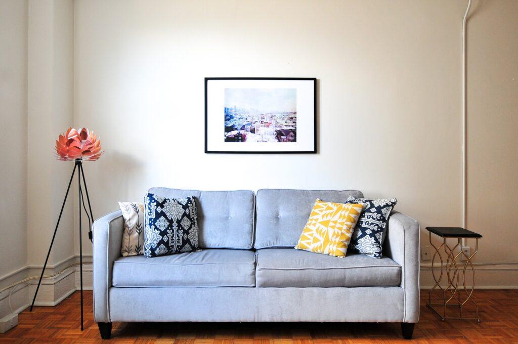 Sala de estar com quadro e abajur. Imagem ilustrativa texto lavagem a seco de sofá.