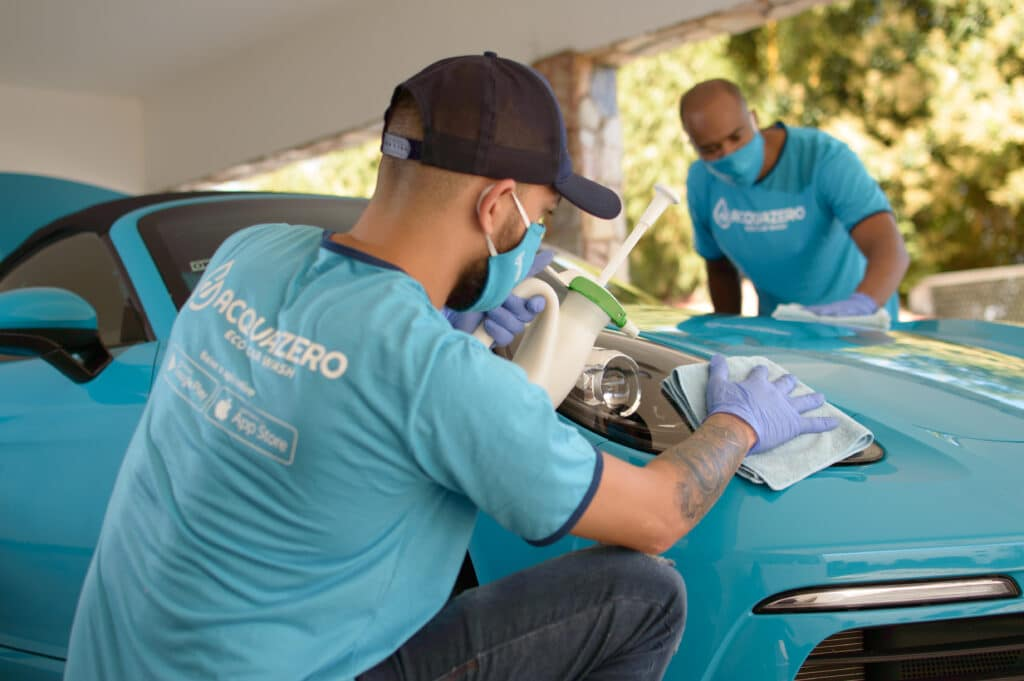 acquazero employees carrying out an ecological car cleaning on the body of a car