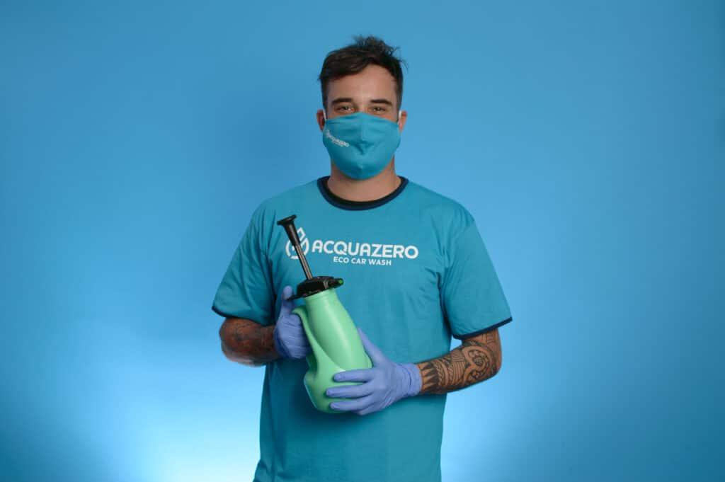 Funcionário da Acquazero usando máscara, blusa e luvas azuis, segura um borrifador. Ilustração do texto como limpar o teto do carro.