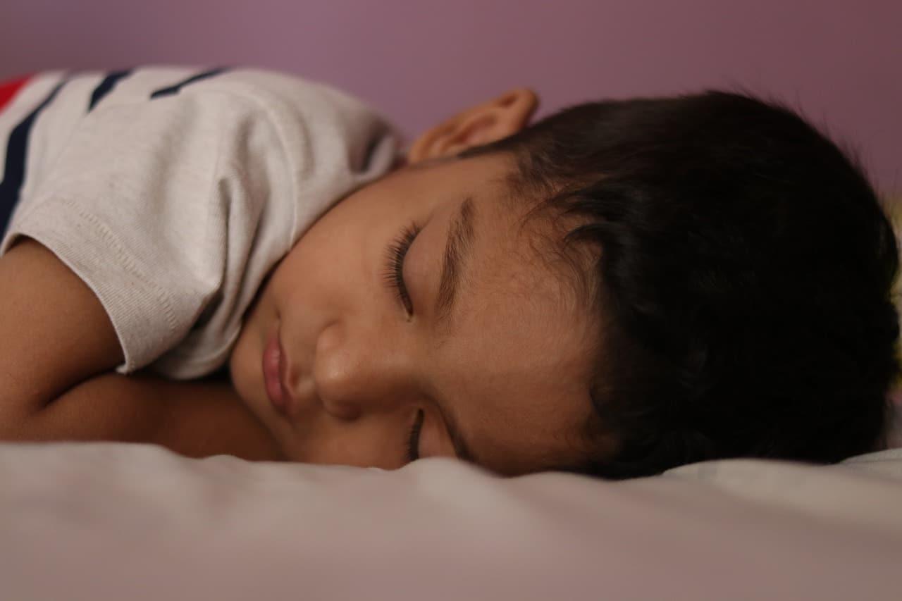 Menino dormindo no colchão. Imagem do conteúdo limpar sofá Betim.