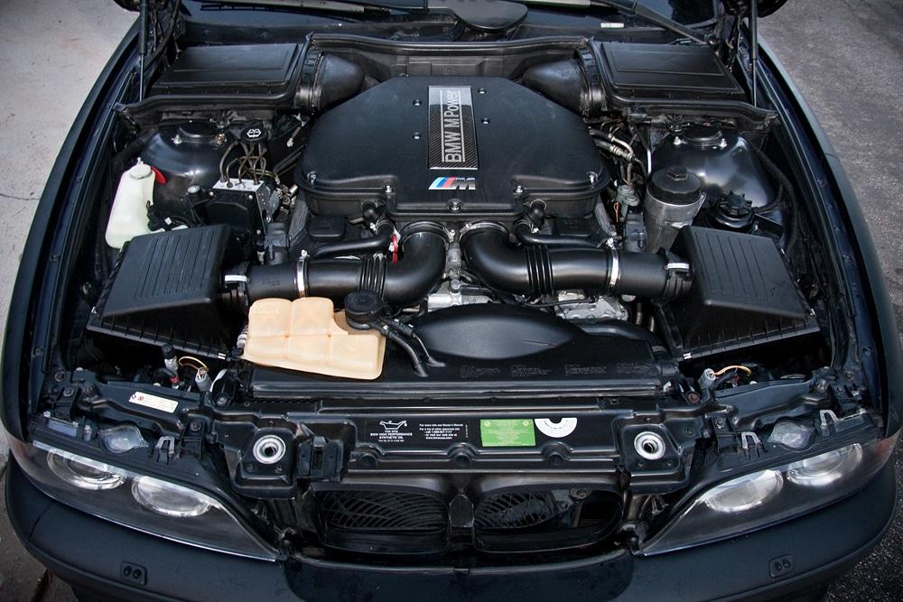 Capô aberto de BMW preta. Imagem ilustrativa texto lavar carro Cristo Redentor.