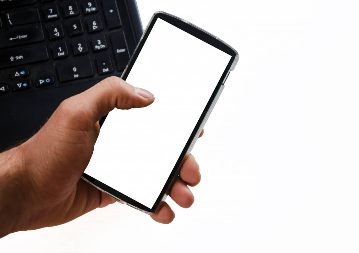 Teclado de notebook ao fundo e mão segurando celular. Imagem ilustrativa texto limpar carro em casa Natal.