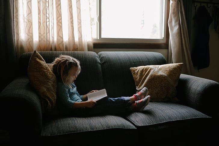 Criança sentada em um sofá, enquanto lê. Ilustração do texto impermeabilização de sofá.