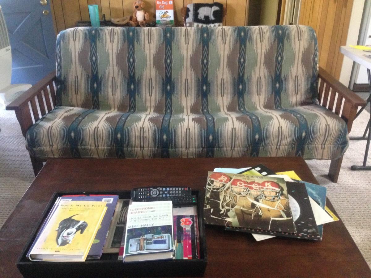 Sofá azul e cinza, com estrutura de madeira. Mesa de madeira com revistas.