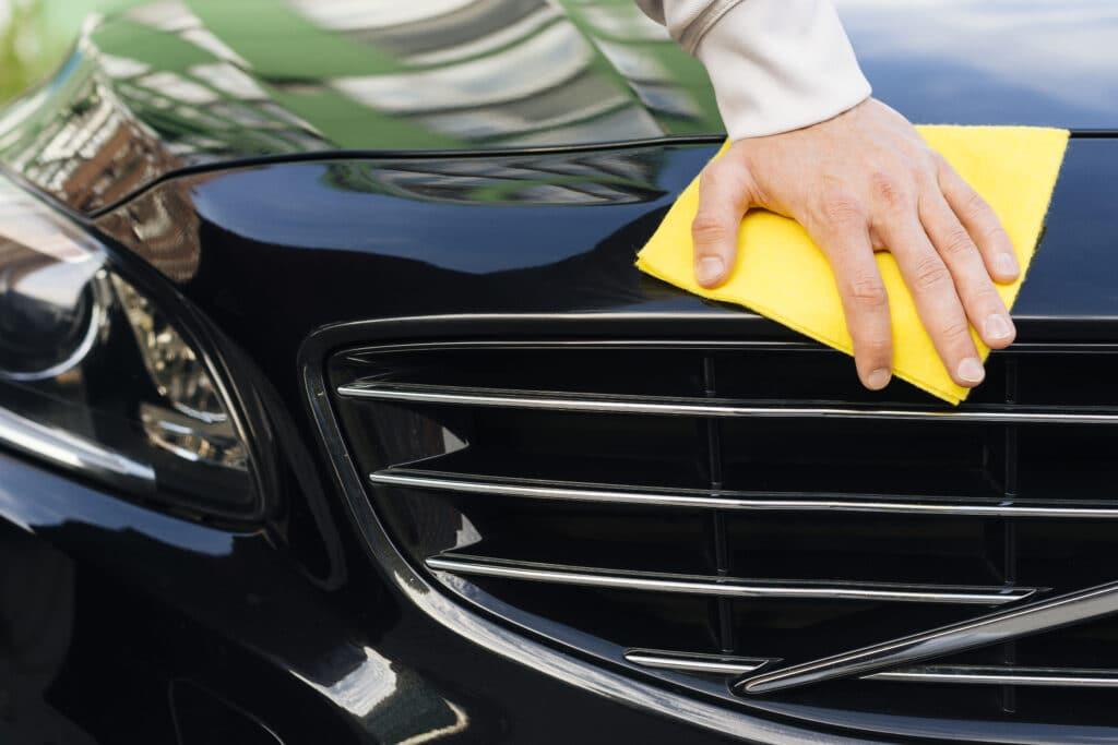 Mão limpando com o auxílio de uma flanela amarela, a parte frontal de um carro preto com detalhes em prata. Ilisutração do texto limpeza de sofá RJ.