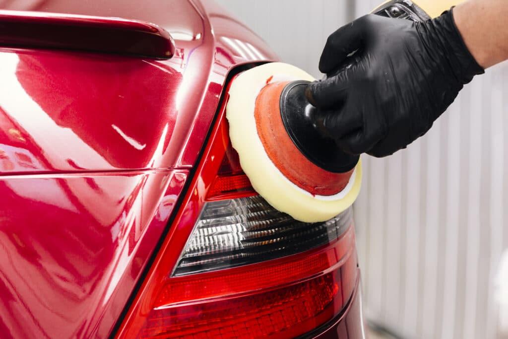 Mão com luva presta limpa o farol traseiro de um carro vermelho com o auxílio de um dispositivo com ponta macia. Ilustração do texto limpeza de sofá RJ.