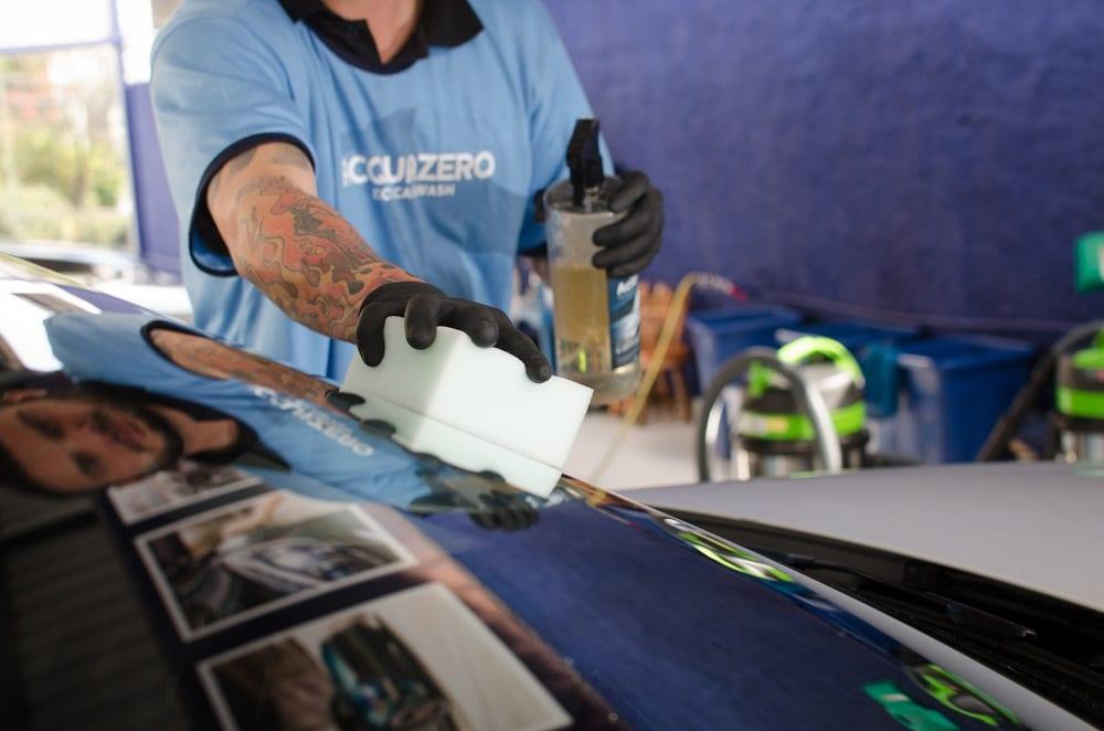 Funcionário da Acquazero de uniforme aplicando produto na superfície de um carro. Imagem ilustrativa para texto maiores franquias brasileiras.
