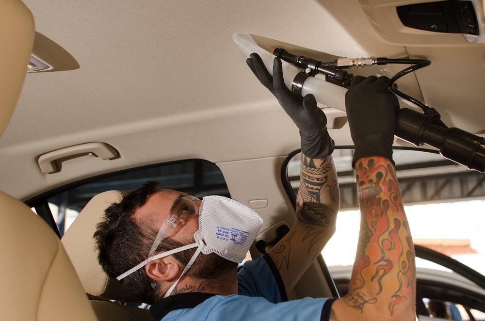 Funcionário da Acquazero de uniforme e equipamento de proteção fazendo a limpeza de teto do carro.