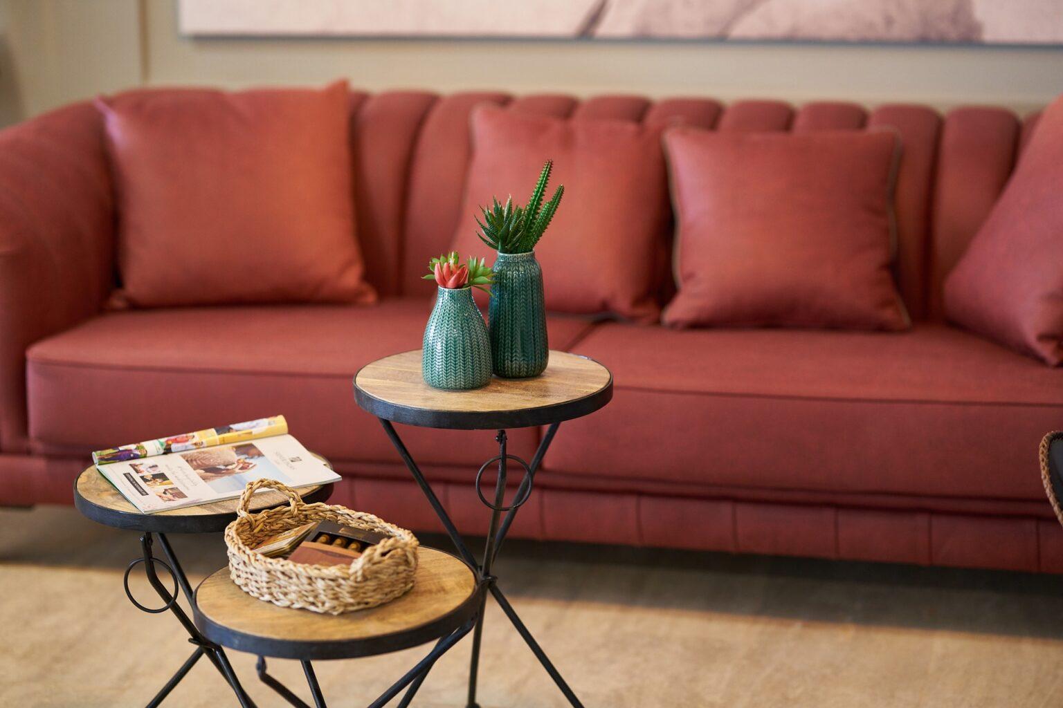 Sofá e almofadas vinho, mesinhas com plantas e cestinha. Imagem ilustrativa texto sofá sujo.