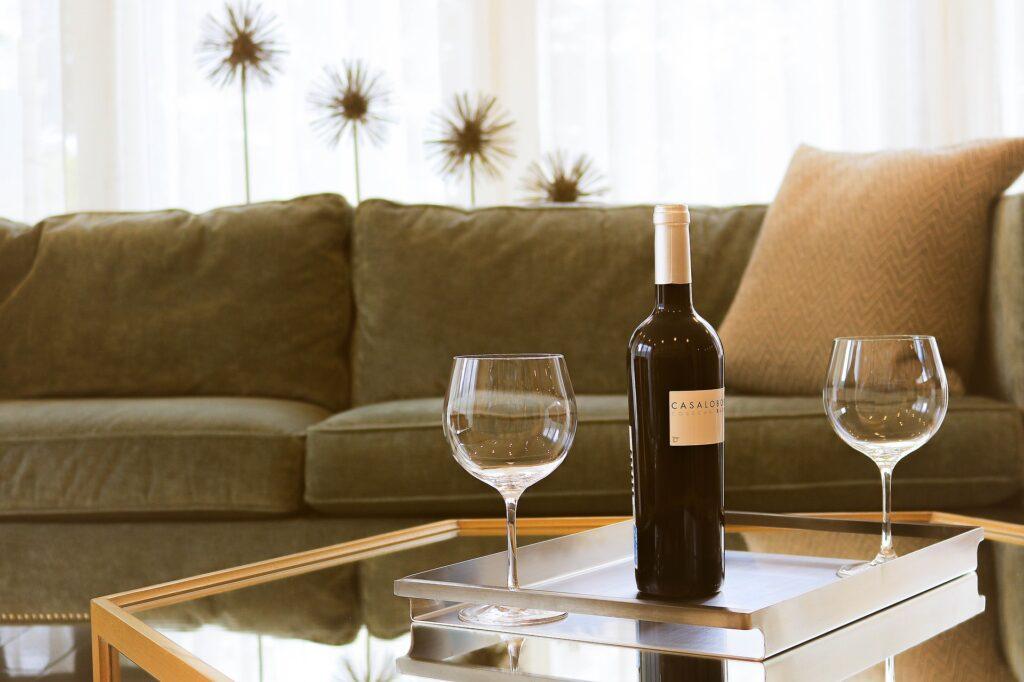 Foto de uma mesa de vidro com uma garrafa de vinho e duas taças, uma em cada lado da garrafa. Ao fundo temos um sofá cinza com almofada bege e cortinas brancas com flores. Imagem ilustrativa para o texto como impermeabilizar tecido.