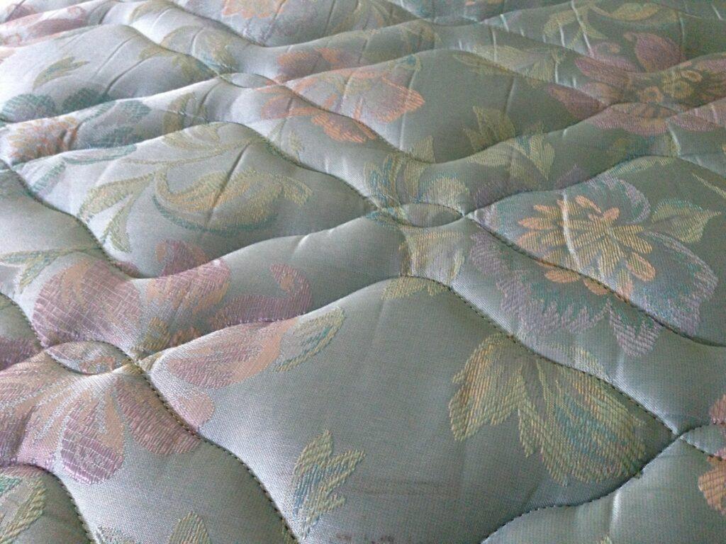 Imagem de um colchão azulado com detalhes de flores laranjas, rosas e amarelas. É possível também perceber as costuras da peça. Imagem ilustrativa para o texto como limpar colchão.