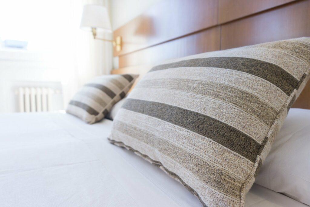 Imagem de uma cama, com lençóis brancos e dois travesseiros com fronhas listadas marrons. A cabeceira da cama é de madeira, ao fundo podemos ver um luminária branca e uma janela aberta em que entra a luz do sol. Imagem ilustrativa para o texto como limpar colchão.