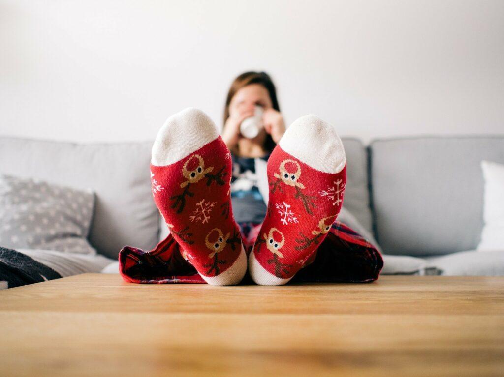 Foto de uma menina sentada em um sofá cinza. A imagem está focada no pé da menina que está em cima de uma mesa. A meia que ela usa é vermelha com desenhos de rena. Imagem ilustrativa para o texto higienização.