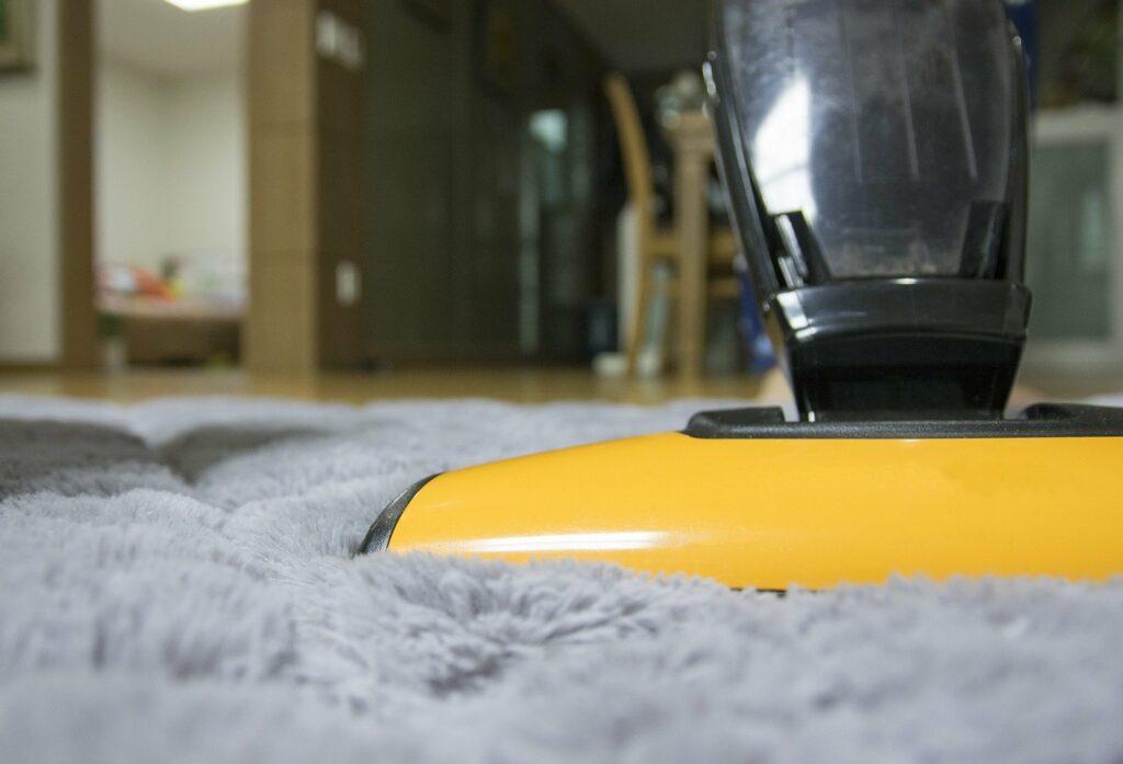 Foto de um aspirador de pó amarelo em contato com um tapete cinza. Ao fundo é possível perceber uma sala com mesa, cadeiras e uma porta. Imagem ilustrativa para o texto higienização.