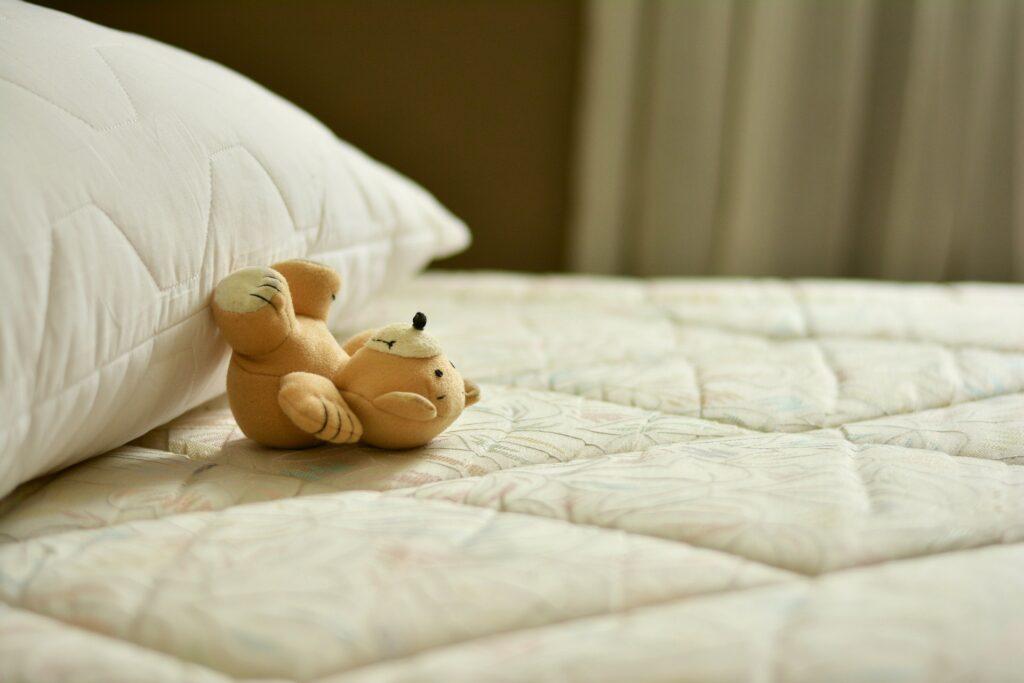 Foto de um colchão branco com um travesseiro também branco do lado e um ursinho de pelúcia bege no meio. Imagem ilustrativa para o texto higienização.