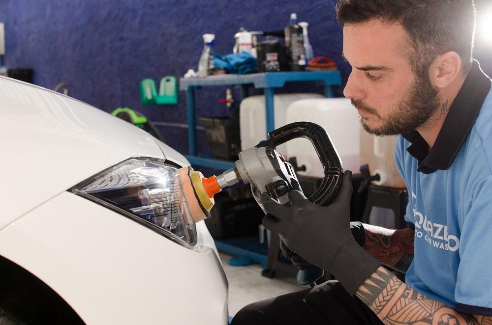 Profissional Acquazero com máquina de polimento trabalhando em um farol de carro branco. Imagem ilustrativa para texto lavar carro Monte Castelo.