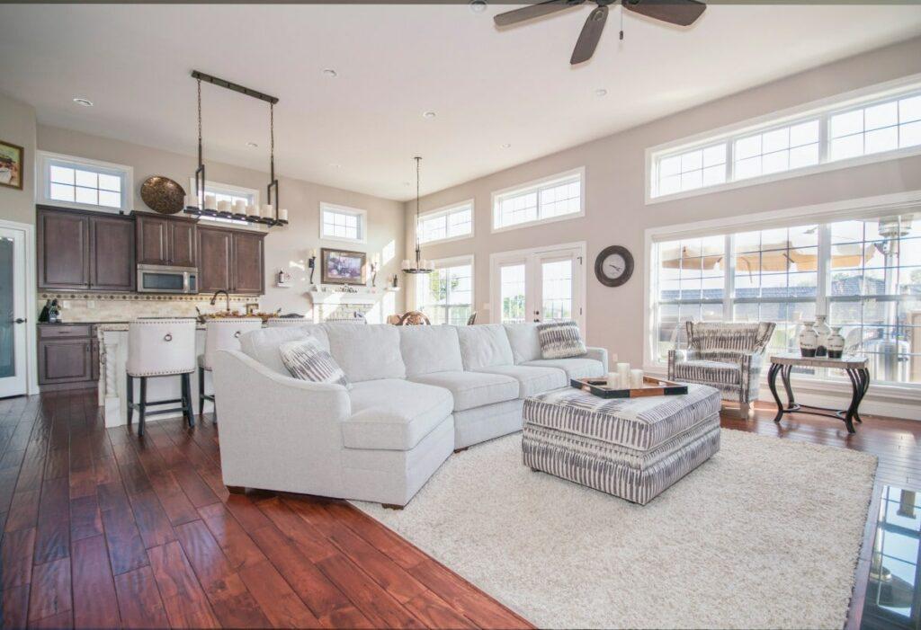 Sofá branco, chão de taco, tapete branco, mesa estofada de centro, ventilador de madeira e janelas até o chão. Imagem ilustrativa texto lavar sofá em Cláudio.