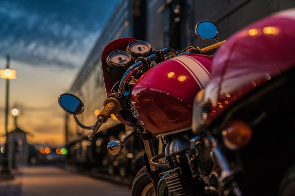 Imagem focada em uma moto vermelha com listra branca ao meio. É possível ver os retrovisores e painel da moto. Ao fundo, temos um galpão e um pôr do sol com alguns focos de luz. Imagem ilustrativa para o texto limpar motor de moto.