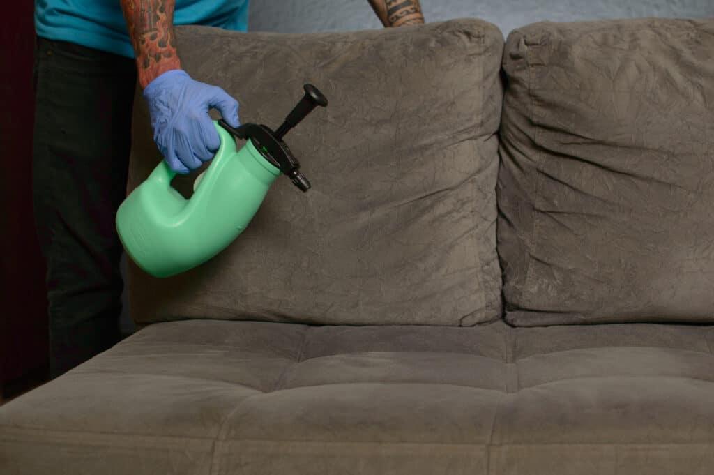 Funcionário da Acquazero com um pulverizador verde na mão fazendo a higienização de um sofá marrom. Imagem ilustrativa para o texto limpar sofá Centro Araguari.