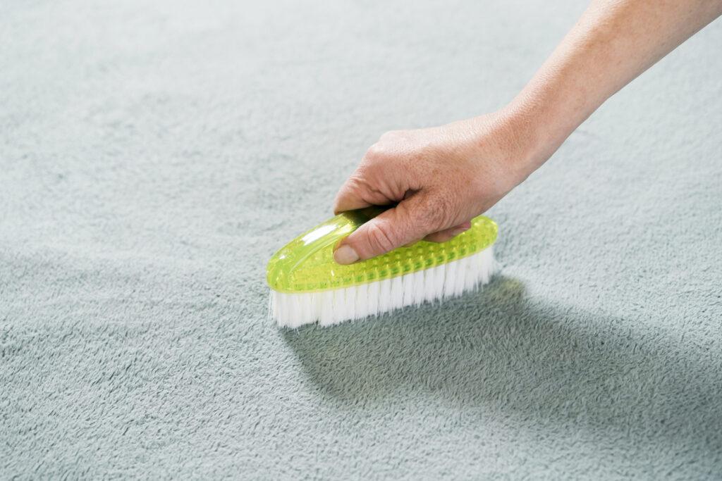 Foto da mão de uma pessoa segurando uma escova de limpeza verde com cerdas brancas. Ela está fazendo a limpeza de um tecido verde água. Imagem ilustrativa para o texto limpeza ecológica.