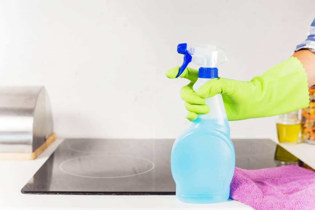 Mão de uma pessoa com luva de limpeza verde segurando um borrifador transparente e azul. Ao fundo vemos um armário com uma superfície preta, uma toalha de limpeza rosa e uma caixa prata. Imagem ilustrativa para o texto limpeza ecológica.
