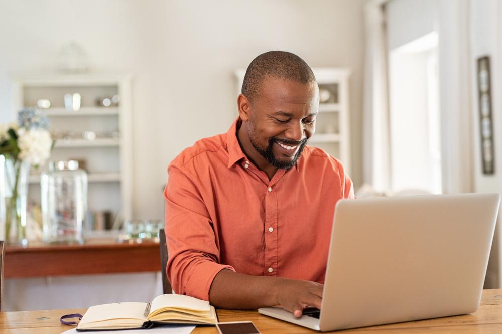 Homem mexendo no computador em sua casa. Ilustração do texto indique e ganhe.