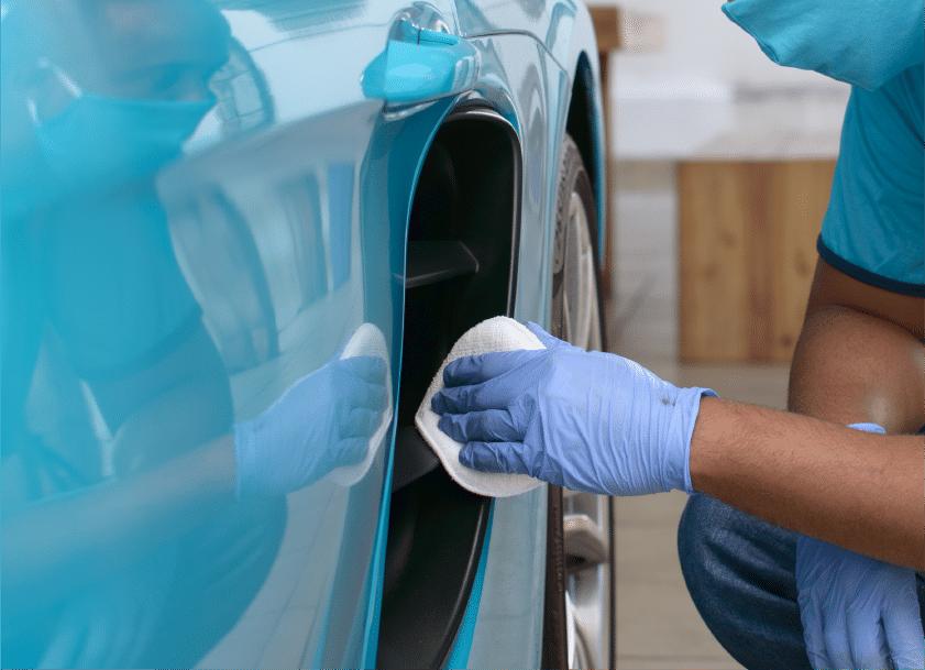 Pessoa com uma blusa e luvas azuis higieniza um carro do mesmo tom com o auxílio de um tecido. Ilustração do texto sobre lavar carro no Vila Nova.