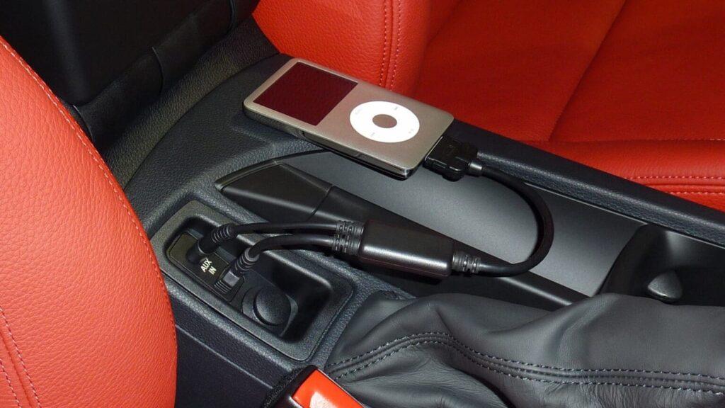 Interior do carro com bancos vermelhos de couro e tocador de MP3 ligado. Imagem ilustrativa texto lavar carro Vila Nova.