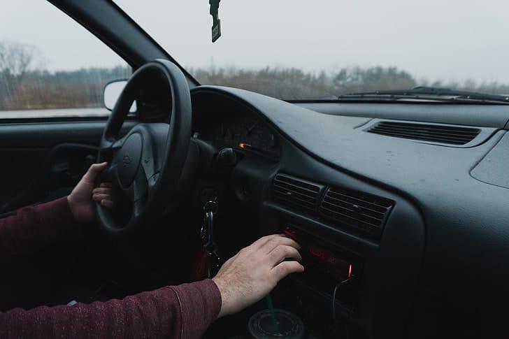 Interior do carro com uma pessoa ao volante. Ilustração do texto sobre como desinfetar o volante do carro.