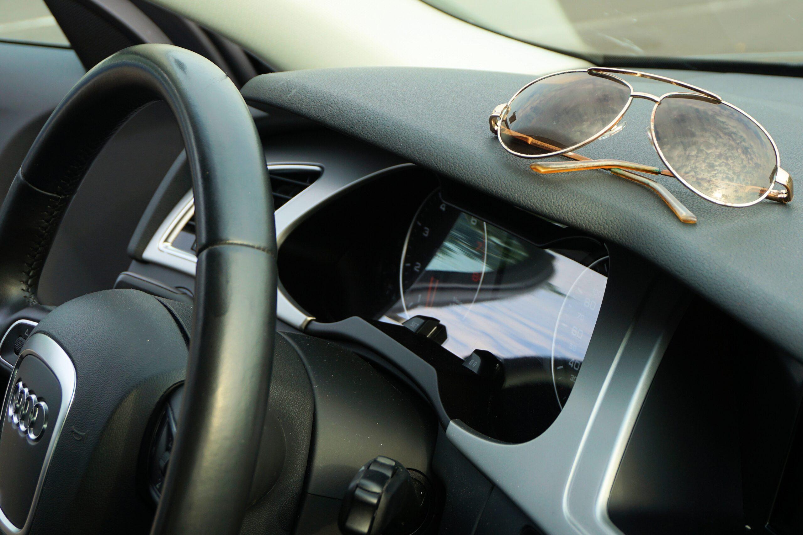 Óculos escuros sobre o painel do veículo. Imagem ilustrativa texto como desinfetar o volante do carro.