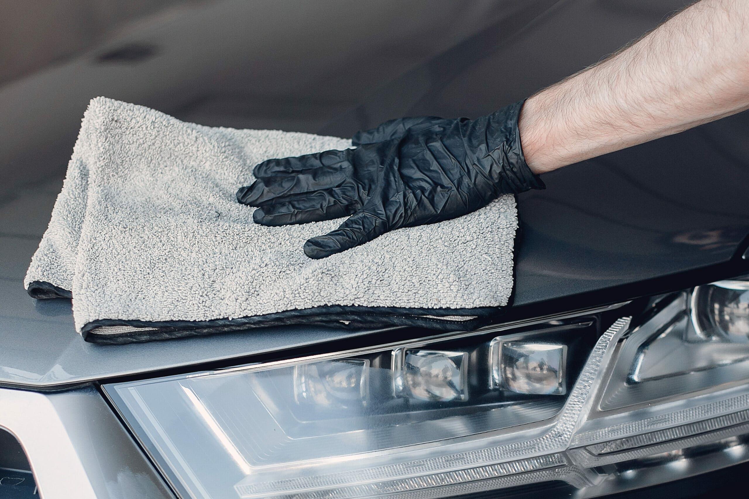 Pessoa com uma luva preta, segurando um pano cinza de microfibra enquanto faz a limpeza da lataria de um veículo. Logo embaixo é possível notar o farol esquerdo do carro. Imagem ilustrativa para o texto lava jato no Parque Bela Vista.