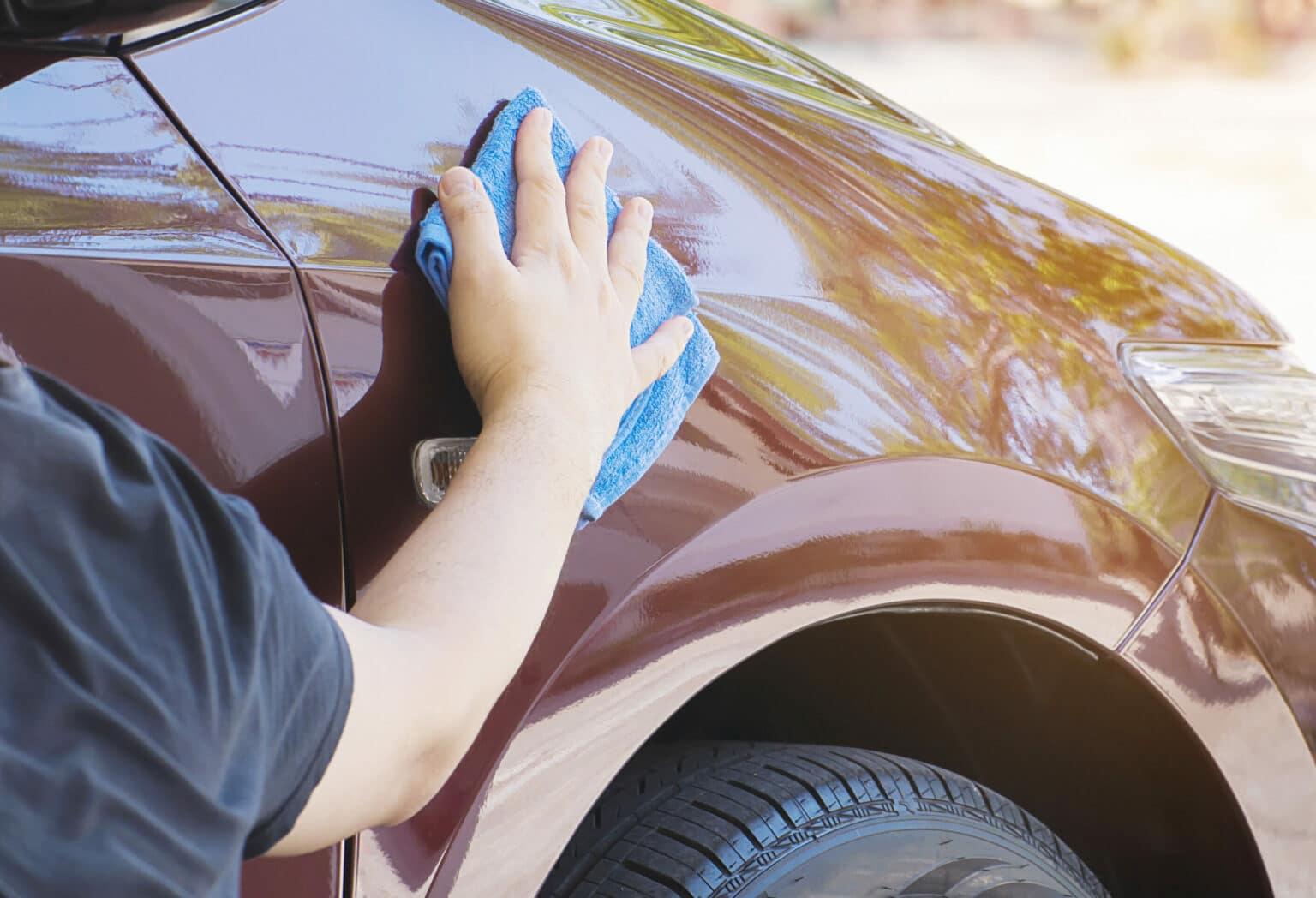Pessoa com blusa preta segurando um pano de microfibra azul realizando a limpeza na lateral de um veículo. O carro é cor vinho e a pessoa está limpando próximo da roda direita. Imagem ilustrativa para o texto lava rápido Centro Patrocínio.