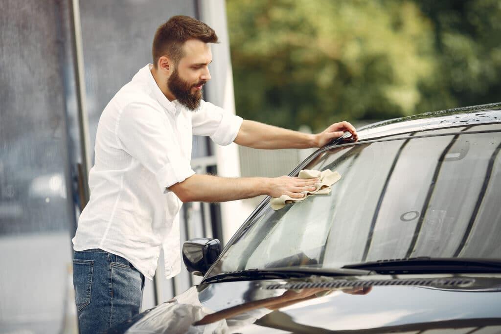 Homem de camisa branca fazendo a limpeza do para-brisa de um carro. Imagem do texto sobre lava rápido no bairro Brasil.