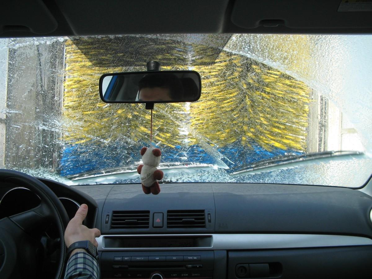 Visão de dentro de veículo em lava rápido automático. Imagem ilustrativa texto lavagem ou limpeza.