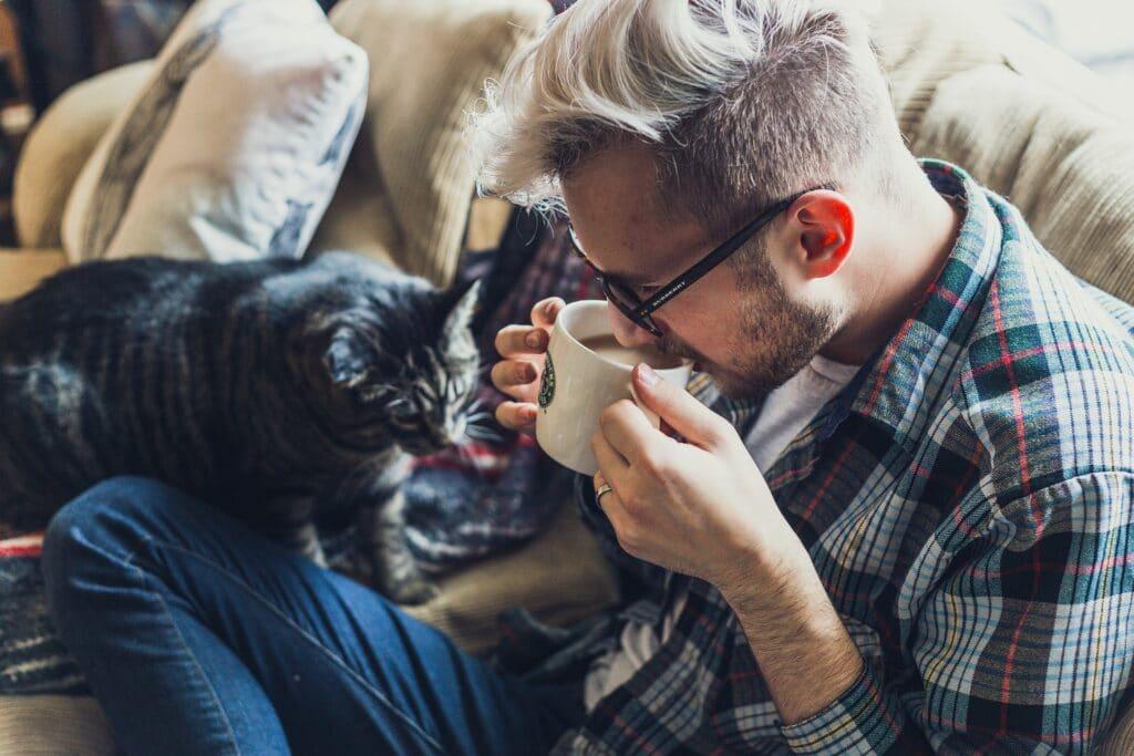 Foto de um rapaz de camisa xadrez e calça jeans, sentado em um sofá com uma caneca na mão. Ao lado dele temos uma gato. O sofá é bege. Imagem ilustrativa do texto limpar sofá Januária.