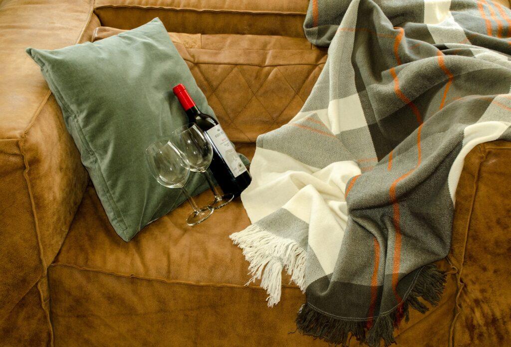 Sofá marrom com uma manta xadrez preta e branca do lado direito. Ao lado esquerdo, temos uma almofada verde, duas taças de vinho e uma garrafa de vidro. Imagem ilustrativa para o texto sofá impermeabilizado em Teresina.