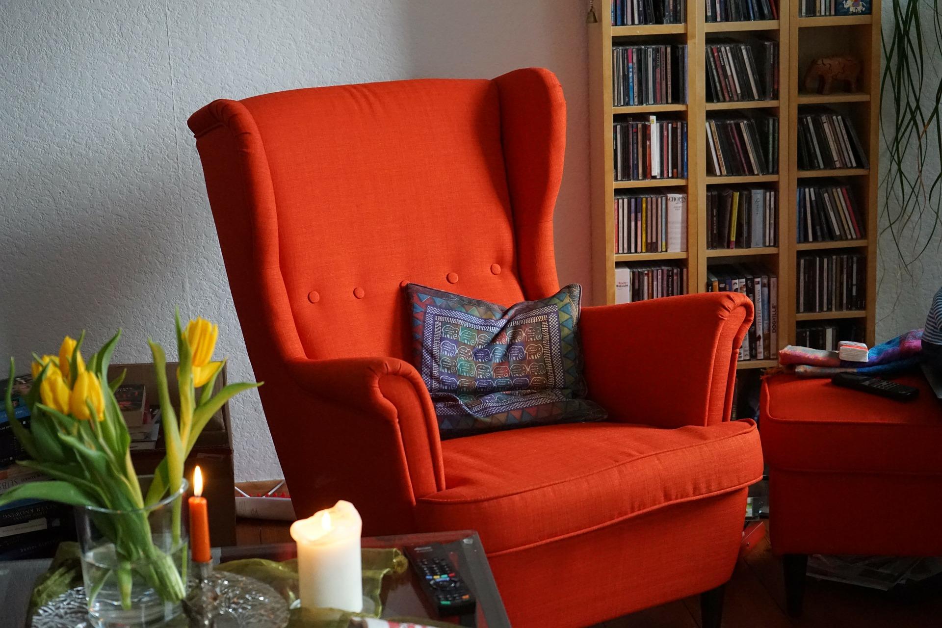 Foto de uma sala com poltrona vermelha no meio e estante ao fundo. Ilustração do texto benefícios da higienização de estofados.