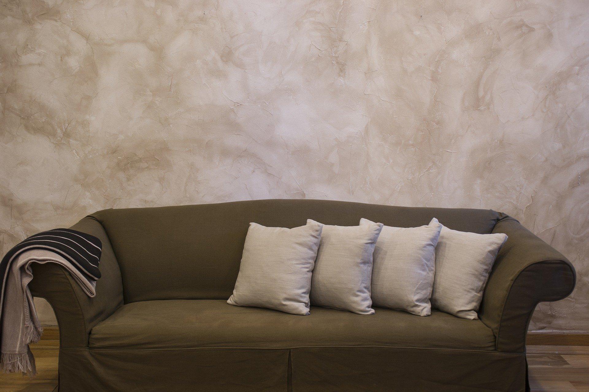 Foto de um sofá marrom com almofadas e uma parede bege ao fundo. Imagem ilustrativa para texto benefícios da higienização de estofados.