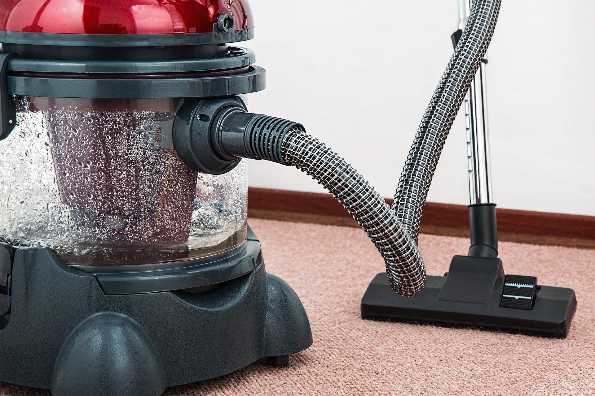 Foto de um aspirador de pó preto em cima de um tapete. Imagem ilustrativa para o texto como limpar carpete de casa.
