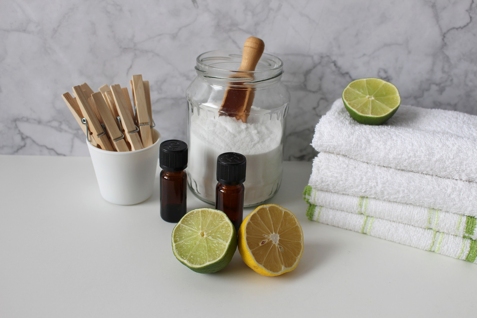 Foto de um pote com bicarbonato, com limões, toalhas e um pote com pregadores. Ilustração do texto sobre como limpar carpete de casa.